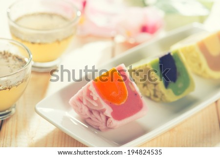 Colorful snow skin mooncakes on white plate with teacup. Chinese mid autumn festival foods.  - stock photo