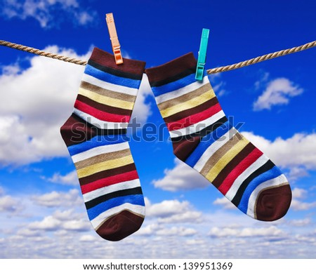 colorful socks hanging on clothespins against the sky with clouds - stock photo