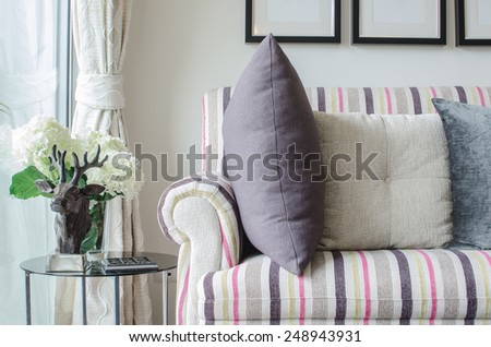 colorful sofa with pillows and glass table in living room at home