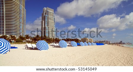 Colorful South Beach Umbrellas with Condos in the background. - stock photo