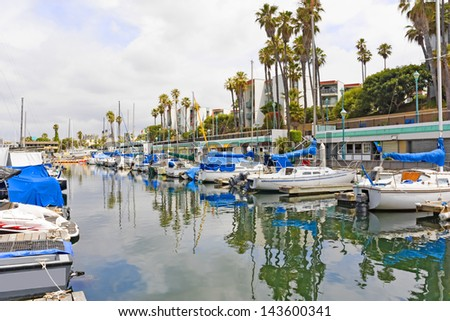 Colorful Southern California marina.Boats in a row at dock.Angled perspective view.Tourist attraction.Buildings, apartments, palm trees, cloudy sky in background. Reflection of sailboats,sky in water - stock photo