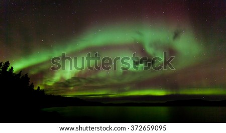 Colorful sparkling show of Aurora borealis or Northern Lights over Lake Laberge, Yukon Territory, Canada