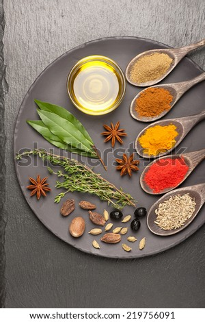 Colorful spices and herbs on dark background - stock photo