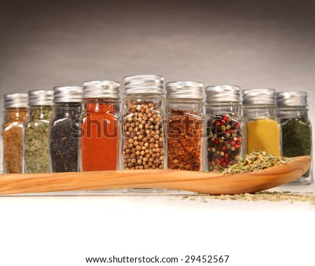 Colorful spices in bottles with wooden spoon - stock photo