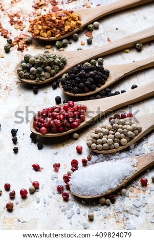 colorful spices in wooden spoons on steel plate
