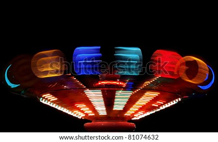 Colorful Spinning Ride at an Annual County Fair with Motion Blur - stock photo