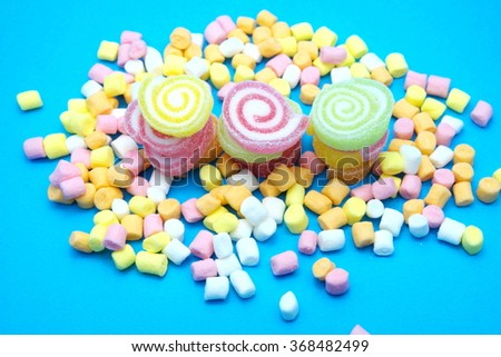 Colorful spiral jelly and colorful marshmallows on blue background. Focus on jelly.    - stock photo