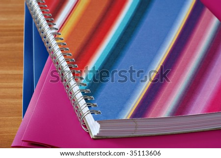 Colorful spiral notebook with matching folders on wood background.  Macro with shallow dof. - stock photo