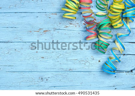 colorful spiral streamers arranged on a rustic old blue wooden background with copyspace