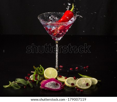 Colorful splash in martini glass from falling red chili pepper, with pomegranate seeds, slices of dragon fruit, green apple, oranges and lemons, on a wet black table - stock photo
