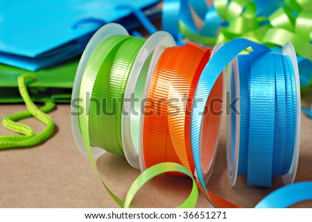 Colorful spools of curling ribbon with gift bags in the background.  Macro with shallow dof. - stock photo