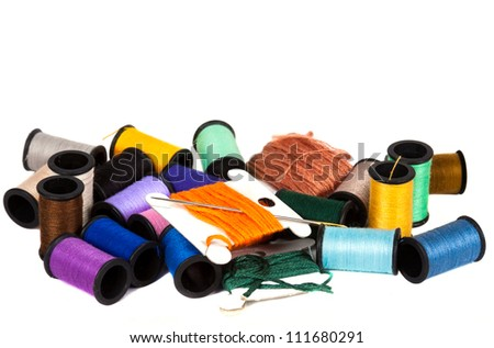 Colorful spools of thread and a needle on a white background