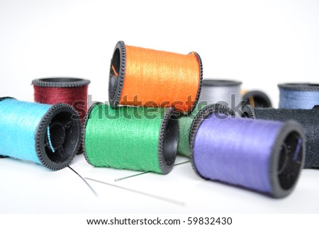 Colorful spools of thread in a random pile with needles. - stock photo