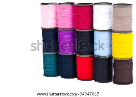 Colorful spools of thread lined up at an angle with a needle. - stock photo