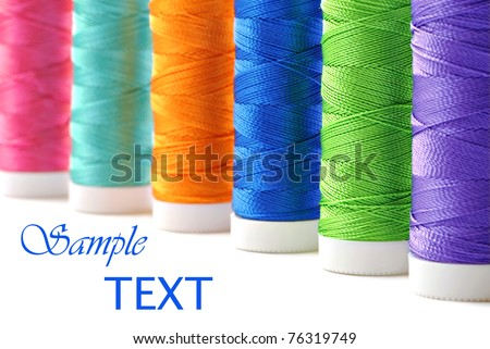 Colorful spools of thread on white background with copy space.  Macro with shallow dof.  Selective focus on green thread. - stock photo