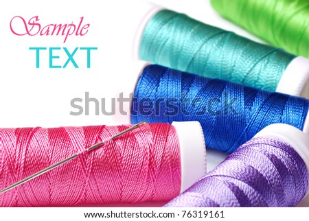 Colorful spools of thread with needle on white background with copy space.  Macro with shallow dof.  Selective focus on eye of needle and pink thread. - stock photo
