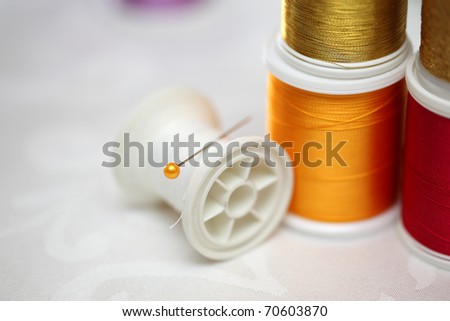 Colorful spools of tread with needle on white background. Shallow DOF. - stock photo
