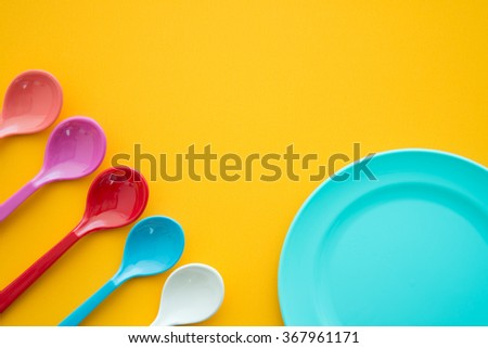 Colorful spoons and dish on yellow table