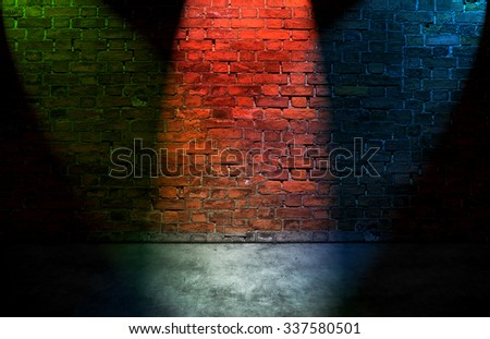 Colorful spot lights on old brick wall - stock photo