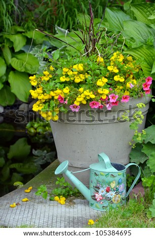 Colorful spring flower planter with decorative watering can