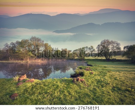 Colorful spring morning in the foggy mountain. Small lake on the foothill. Retro style. - stock photo