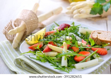 Colorful spring salad with fresh white asparagus, rocket salad and strawberries - stock photo