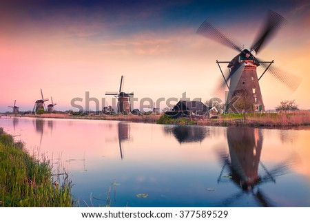 Colorful spring scene in the famous Kinderdijk canals with windmills, UNESCO world heritage site. Sunset in Dutch village Kinderdijk, Netherlands, Europe.