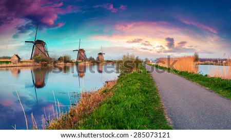 Colorful spring sunset in Netherlands. Dutch windmills on canal at Kinderdijk, an UNESCO world heritage site. - stock photo