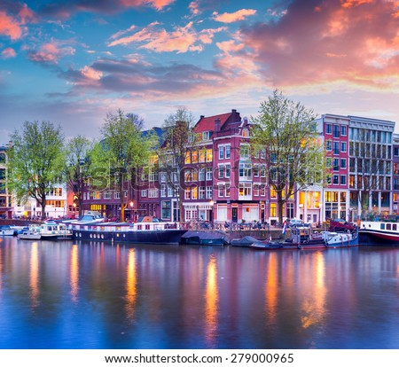 Colorful spring sunset on the canals of Amsterdam. Authentic Dutch architecture in the capital and most populous city of the Netherlands. - stock photo