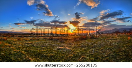 Colorful spring sunset with Sun rays coloring the clouds - stock photo