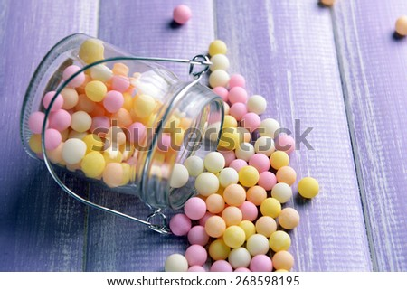 Colorful sprinkles on jar on table close-up - stock photo