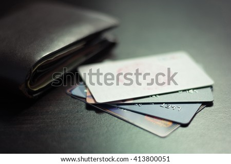 Colorful stack of credit cards and shopping gift cards  with wallet on gray carpet back ground. Extremely shallow dof. - stock photo