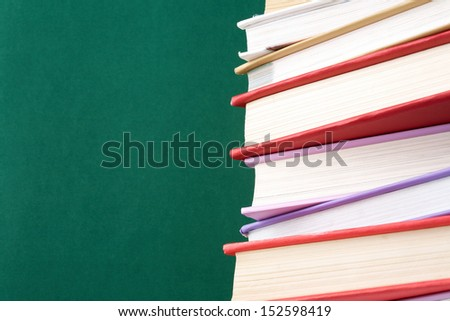 Colorful stack of textbooks on background of blackboard - stock photo