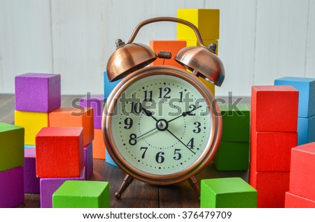 Colorful stack of wood cube building blocks and alarm clock