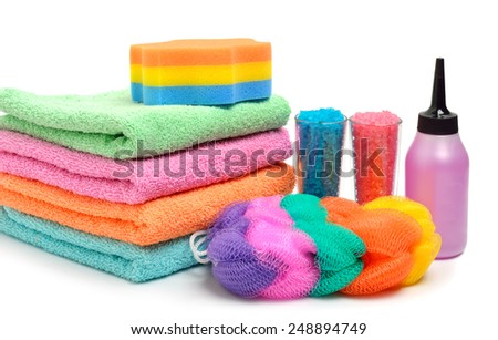Colorful stacked spa towels, sea salt, mop and shampoo bottle isolated on white