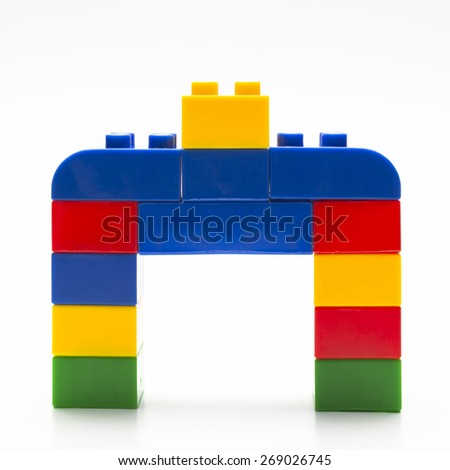 Colorful stacked toy building blocks with shape of house.