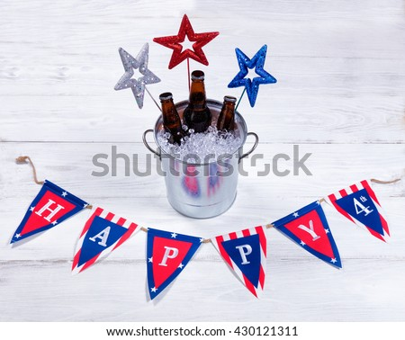 Colorful stars, banner and a bucket of ice with bottled beer on rustic white wood. Fourth of July holiday concept for United States of America.