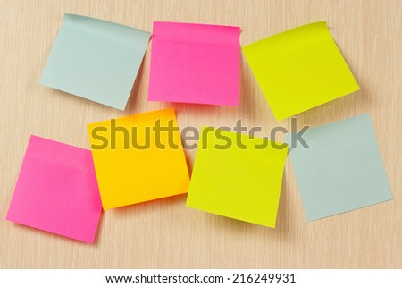 Colorful stickers on a wooden board from notice - stock photo