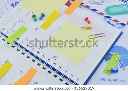 Colorful sticky notes and pin on business diary page - stock photo