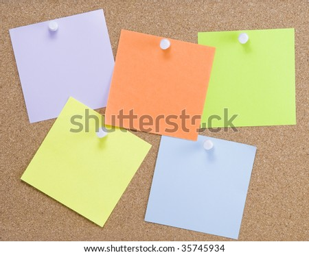 Colorful sticky notes attached to a cork board with white thumbtacks