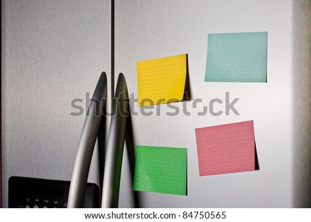 Colorful sticky notes on a stainless steel refrigerator door - stock photo