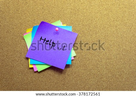 colorful sticky notes on cork bulletin board and write the words HELP. - stock photo