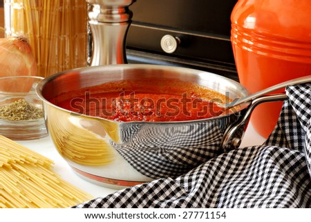 Colorful still life of freshly prepared spaghetti sauce with pasta and additional ingredients in background.  Close-up with shallow dof. - stock photo