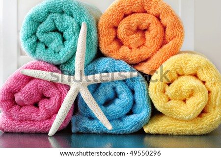 Colorful still life of towel rolls with white finger starfish on reflective surface. - stock photo