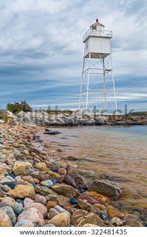 Colorful stones lining the water's edge lead the eye to the metal tower lighthouse at the harbor town of Grand Marais in Michigan's Upper Peninsula. - stock photo