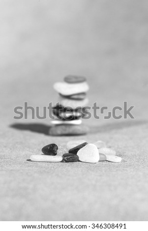 Colorful stones on the ground. This image shows that every individual is important for the whole team metaphorically speaking. A pile of stones in the background. Image in black and white. - stock photo