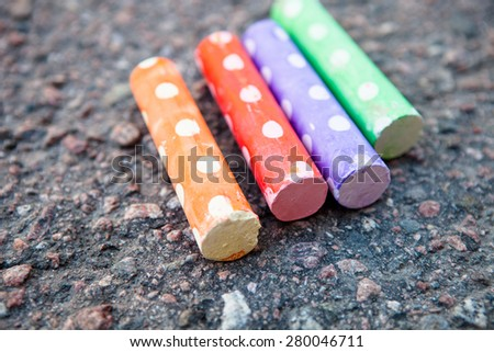 Colorful street chalk on asphalt outdoors - stock photo
