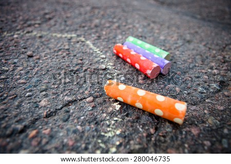 Colorful street chalk on the ground on asphalt - stock photo