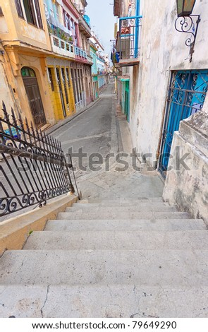 Colorful street in Old Havana sidelined with decaying buildings - stock photo