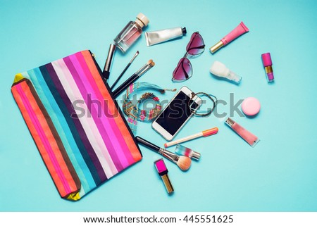 Colorful striped  bag with woman accessories , cosmetic and brushes on trendy turquoise background.   - stock photo
